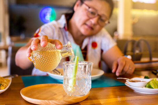 Selective focus to hand of Asian female customers pouring Lemongrass juice into a glass. The concept of a refreshing drink from nature.