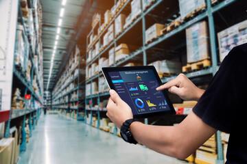 Obraz Smart warehouse management system.Worker hands holding tablet on blurred warehouse as background - fototapety do salonu