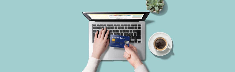 ノートパソコンで、クレジットカード番号を入力している女性の手。ネットショッピングのイメージ。真上からのアングル
