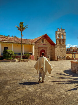 Sunny day. Vertical photo. Peasant walks through the main park of Sora in Boyacá, Colombia with church in the background