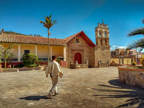 Horizontal photo of a peasant walking through the main park of Sora in Boyacá, Colombia with church in the background