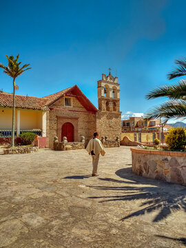 Peasant walks through the main park of Sora in Boyacá, Colombia with church in the background