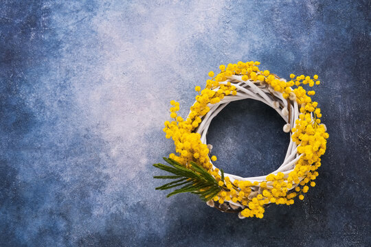 Easter background. Easter wreath decorated with mimosa flowers on blue background. Top view, copy space