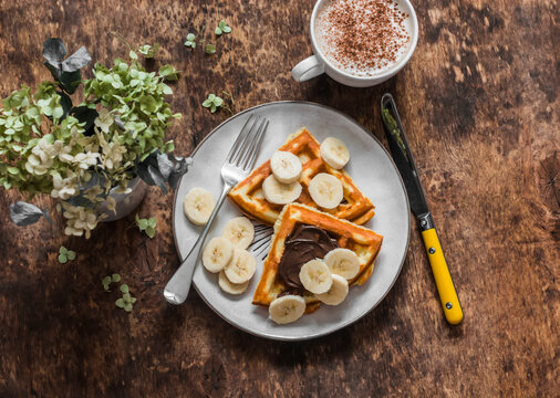 Cottage cheese waffles with chocolate paste, banana and cappuccino on a wooden background, top view. Delicious breakfast, dessert