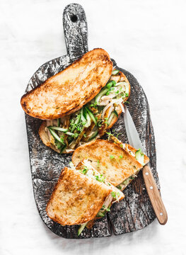 Sandwiches with turmeric grilled chicken, cucumber, microgreens and homemade mustard mayonnaise sauce on a wooden cutting board on a light background. Delicious tapas, snack, breakfast, appetizers