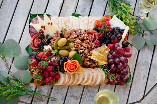 Elegant charcuterie grazing board filled with assorted meats , cheeses, fruits, nuts, olives, and garnishes