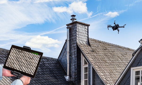 Drone in the air inspecting the roof of the house. Close-up of drone, monitor  and roof.