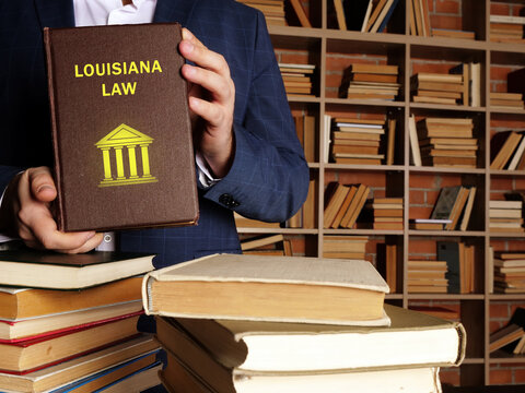 Jurist holds LOUISIANA LAW book. Louisiana residents are subject to Louisiana state and U.S. federal laws