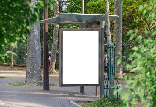 Bus stop billboard Mockup in empty street in Paris. Parisian hoarding advertisement close to a park in beautiful city