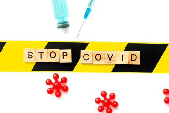 """Wooden letters form the inscription """"Stop Covid"""". Vial with vaccine, syringe and microbes on a white background."""