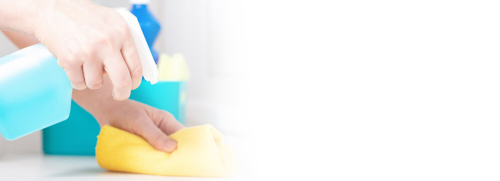 Woman cleaning table with blue color disinfectant spray and yellow towel. Banner with white copy space. Cleaning supplies. Surface wipe. Close up.
