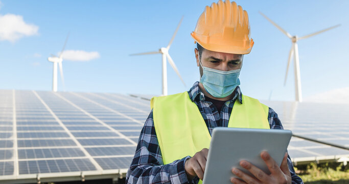 Man worker using digital tablet while wearing safety mask at renewable energy farm during coronavirus outbreak - Soft focus on face