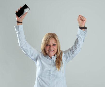 mujer ganadora feliz con los brazos levantados y el teléfono  en la mano