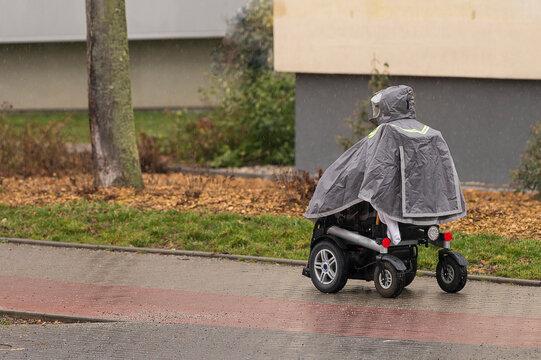 Elektrischer Rollstuhl bei Regen mit Regenschutz