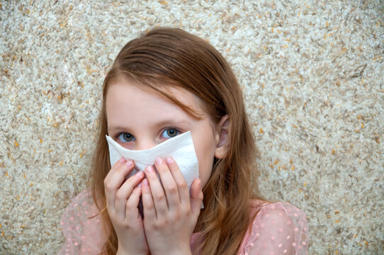 Child girl with a cold virus wipes his nose from a runny nose