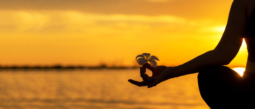 Close up Silhouette hands. Woman do yoga outdoor. Woman exercising vital and meditation for fitness lifestyle club at the sunset beach background. copy space for banner