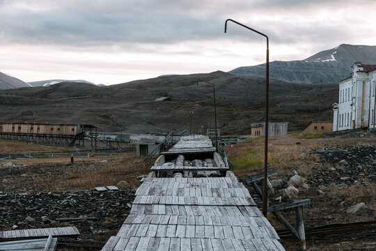 Ruined buildings and walkway with mountain in the background in the Ghost Town of Pyramiden, Svalbard