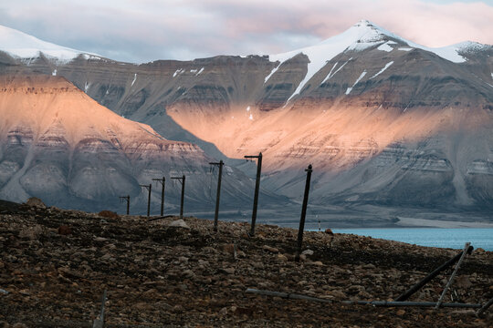 Ruined telephone poles with snow capped mountains in the background in the Ghost Town of Pyramiden, Svalbard during sunset