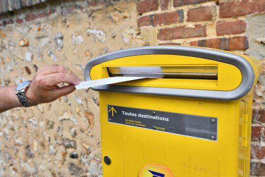 La Poste. Main qui poste une lettre dans une boite aux lettres