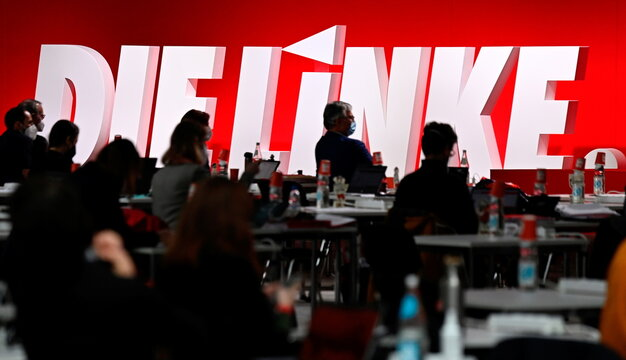 """Silhouettes of party members are seen in front of the logo of the left wing """"Die Linke"""" (The Left) party during the party congress in Berlin"""