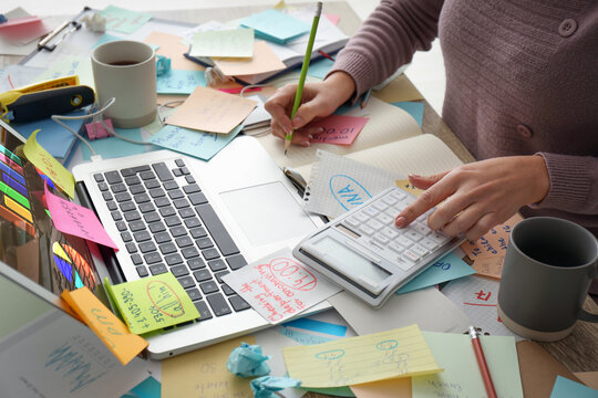 Overwhelmed woman working at messy office desk, closeup