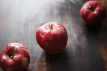Obraz Jabłka czerwono mokre na brązowym stole - fototapety do salonu
