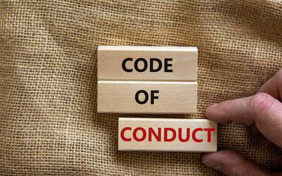 Code of conduct symbol. Concept words 'Code of conduct' on wooden blocks on a beautiful canvas background. Businessman hand. Business and code of conduct concept. Copy space.