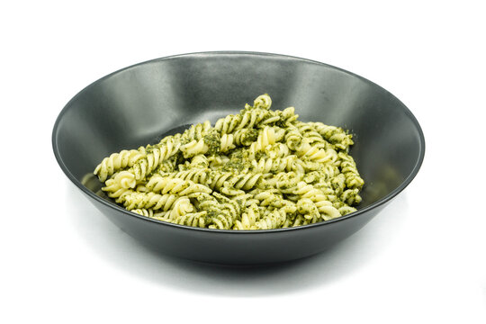Plate of pasta with pesto isolated on white background
