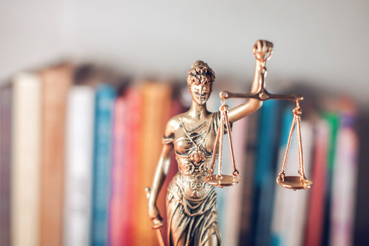 lady justice and books in the background