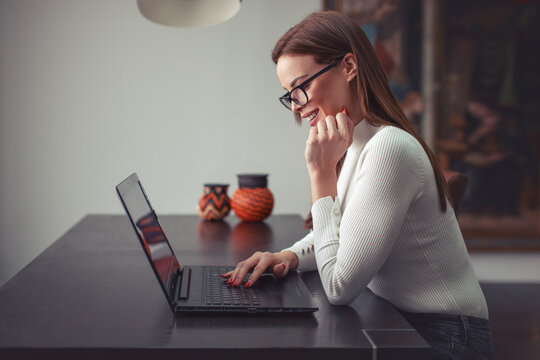 Happy young smart woman communicating by laptop