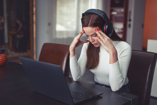 Young tired smart woman in headset has headache at laptop