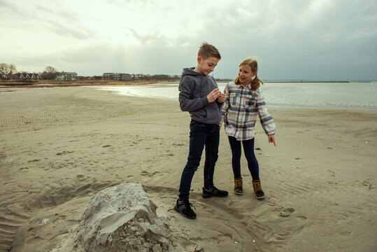 Two happy teenager children siblings walking on Baltic sea beach in spring