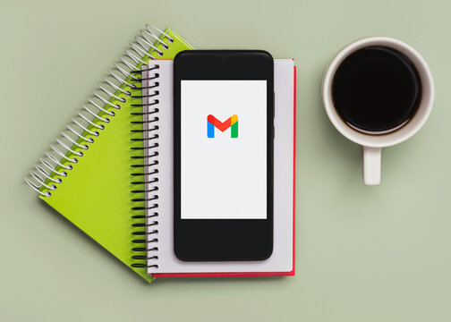 Gmail logo on black screen of smartphone with notebooks and cup of coffee