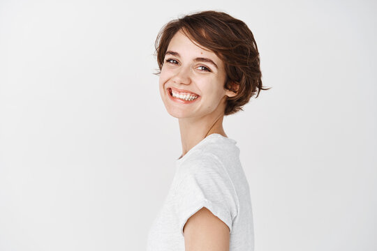 Natural young woman with happy smile, turn head at camera and looking cheerful, standing against white background in t-shirt