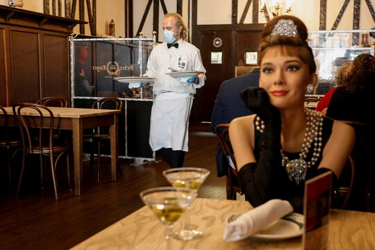 Madame Tussauds's wax figure of Audrey Hepburn sits at an empty table at Peter Luger Steak House in Brooklyn, New York