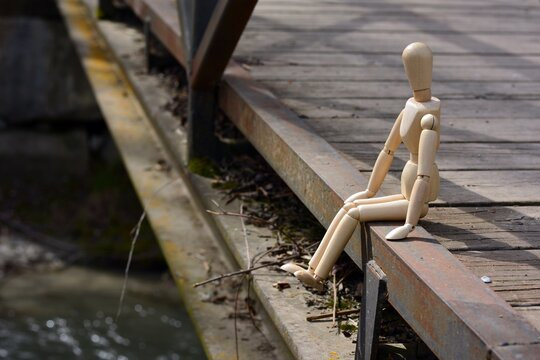 Maniquí de madera sentado en el puente de un río