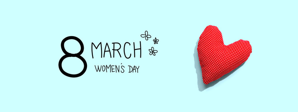 Happy womens day message with a red heart cushion - flat lay