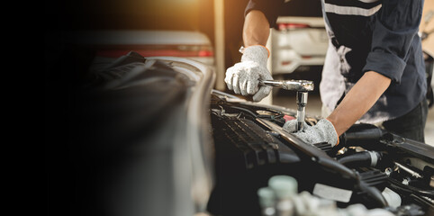 Obraz Automobile mechanic repairman hands repairing a car engine automotive workshop with a wrench, car service and maintenance,Repair service. - fototapety do salonu