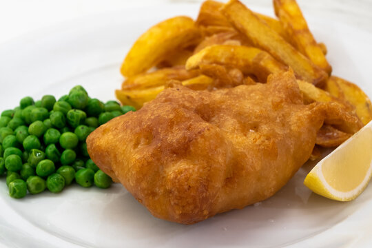 Fish and Chips with Peas and Lemon on a White Plate, a Typical Traditional Dish of English Cuisine with Deep Fried Cod and Fries