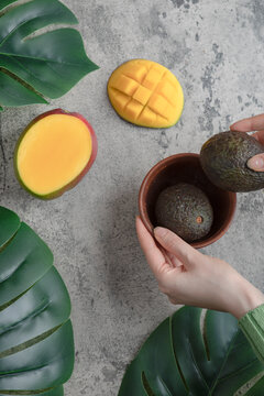 Female hands picking ripe avocados from bowl on marble surface