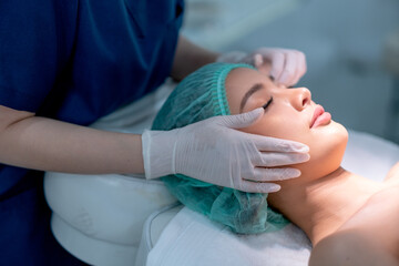Fototapeta Beauty clinic hands touch on face of customer woman who lie on bed with light during process of treatment.