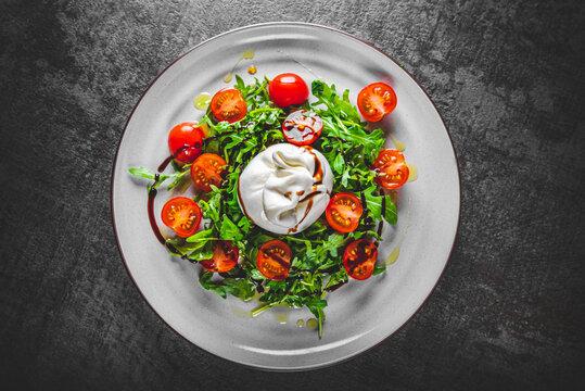 salad with burrata cheese, arugula salad and tomatoes on plate on Dark grey black slate background