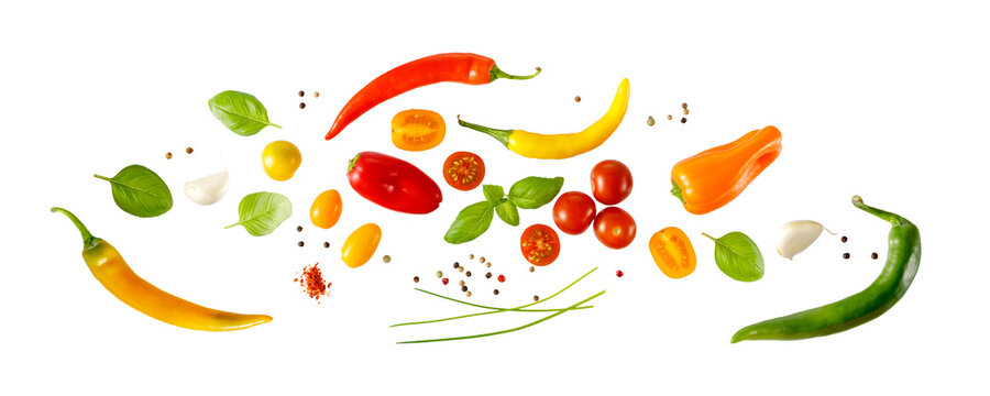 Mediterranean healthy food vegetarian ingredients isolated on white. Cherry tomatoes, basil leaves, color chilli peppers, garlic, green onion flying  on white. Vegetable banner