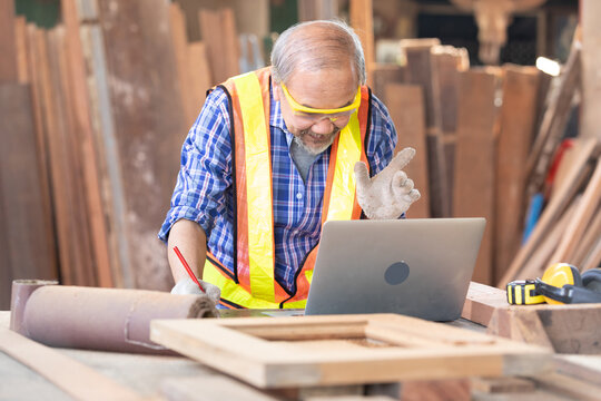 senior carpenter or worker using laptop computer and talking to someone