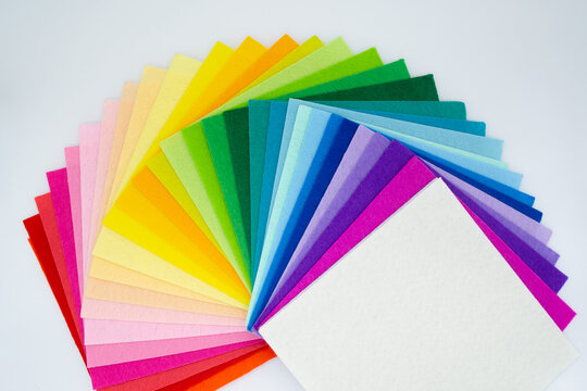 The square pieces of felt spread out by a color spectrum on similarity of a rainbow from white to red
