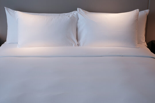 Clean Bedding sheets and pillow on natural wall room background. White bedding and pillow in hotel room. White pillows on empty bed.