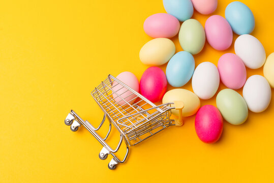 Top view photo of shopping trolley with copyspace over yellow background.