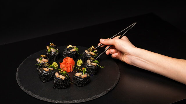 Hand with chopsticks holds a sushi. Custom sushi roll with black rice, crab meat, avocado, smoked salmon mousse, oar caviar, masago, shrimp cocktail, edible gold leaf, ginger, wasabi on black table.