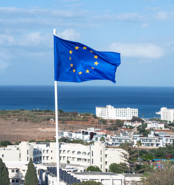 European Union flag on background of resort town and sea in Republic of Cyprus
