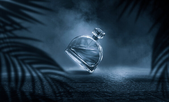 Women's Perfume in a glass bottle on a dark natural empty stage, wet asphalt, close-up. Sunlight, palm branch, shadow.